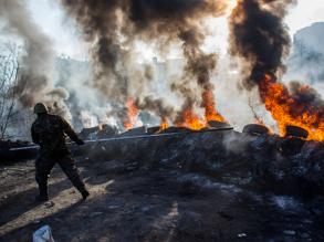 Сторонник радикальной оппозиции подбрасывают автомобильные покрышки в огонь на баррикаде Институтской улице в Киеве. Фото: РИА Новости